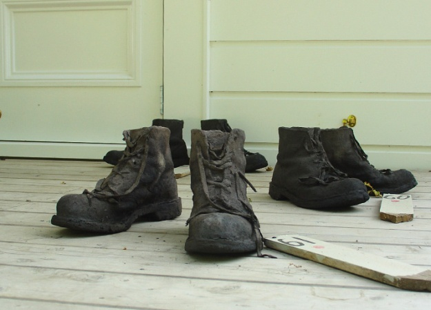 Carbon Boots, Recycled, pulped newspaper, fabric and clay transformed into charcoal. 19 x 24 x 32 cm each pair x 7